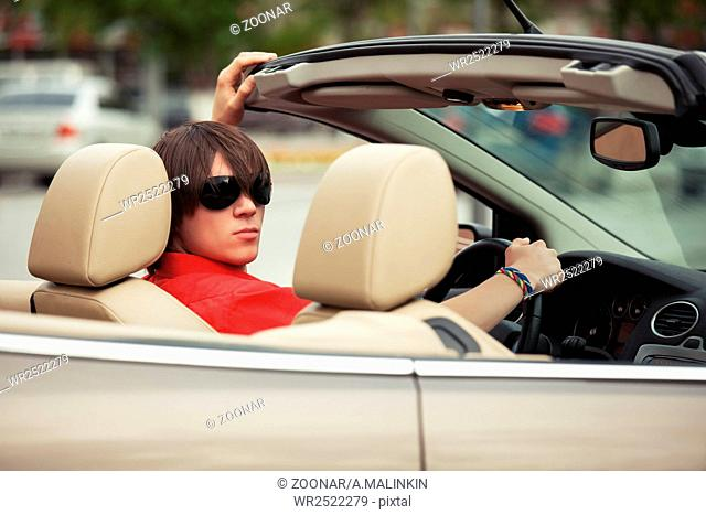 Young man in sunglasses driving convertible car
