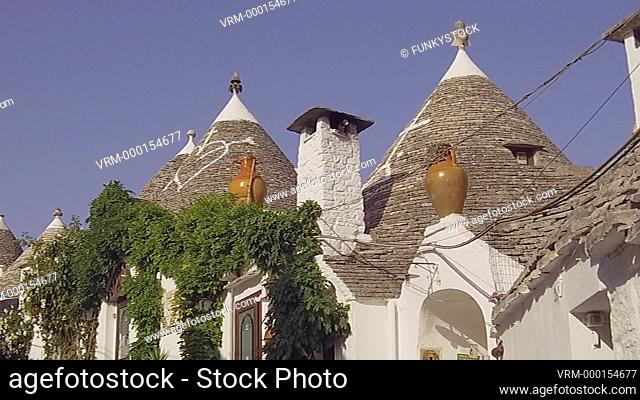 Alberobello, Apulia, Italy : zoom out of a street of conical beehive shaped stone built historical trullo traditional houses of Alberobello