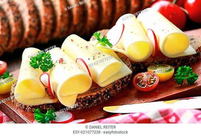 Gouda cheese rolls on an open vegetarian sandwich