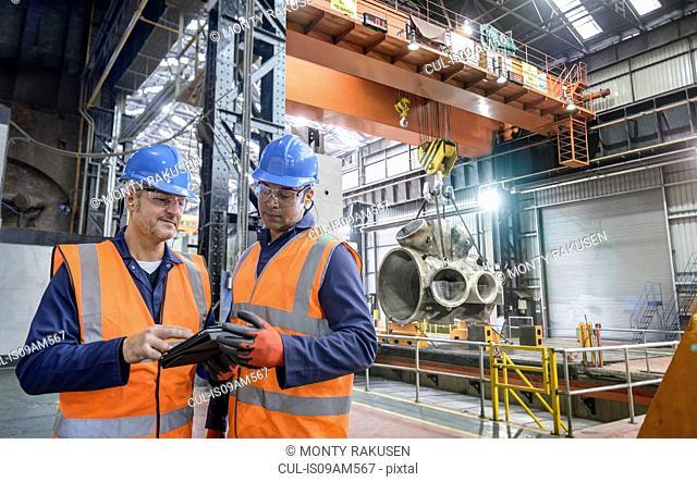 Steelworkers using digital tablet in engineering factory