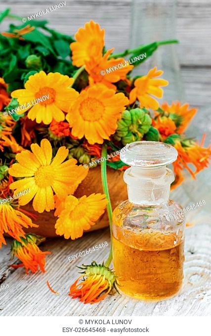 bottle of medicinal tincture of calendula flowers in folk recipe