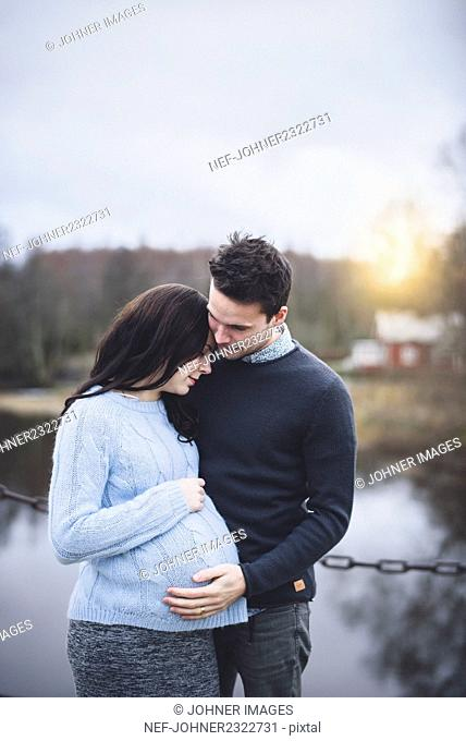 Man embracing pregnant woman outdoors