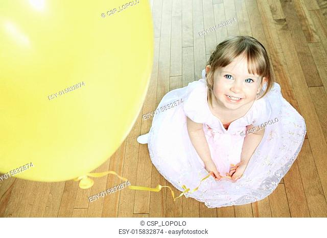 A nice little girl sit on the floor with a balloon