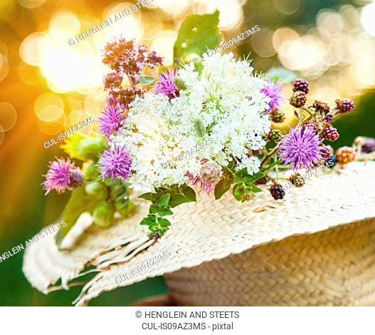 Freshly picked wildflowers with hazelnut and blackberry plants in straw hat