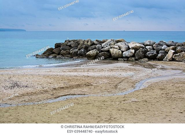 Water, rocks, seagull and meandering water on sandy tranquil Mediterranean winter beach in Mallorca, Balearic islands, Spain in February