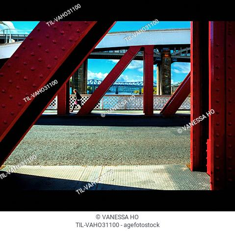 Female youth walking over large metal bridge in day light