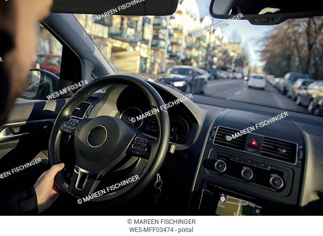 Steering wheel and hand of a man driving a car through the city