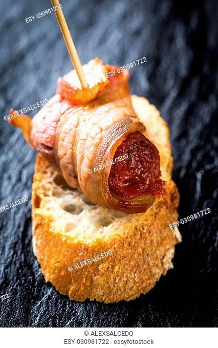 Typical spanish tapas: Delicious pork sausage called chistorra with bacon