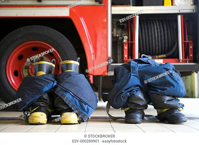 Two firefighting uniforms on floor by fire engine