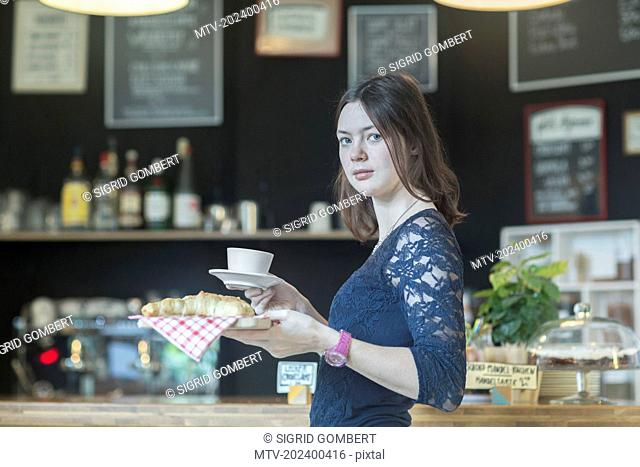 Young waitress serving coffee and croissant in coffee shop, Freiburg Im Breisgau, Baden-Württemberg, Germany