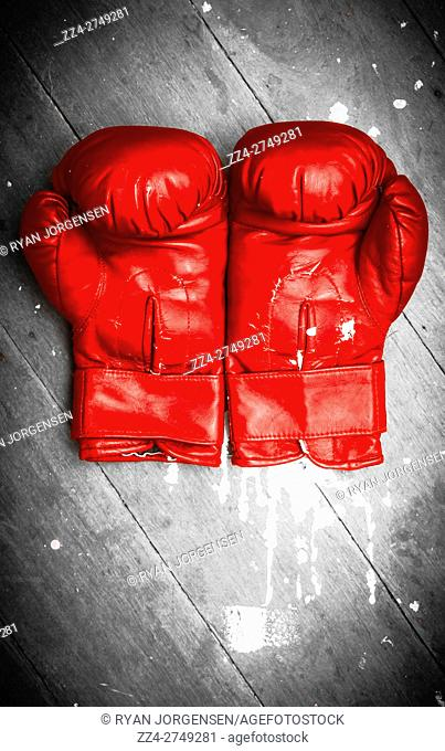 Close-up of vivid red boxing gloves on grey wooden background. Match ring still-life