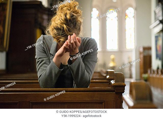 Tilburg, Netherlands. Young woman, praying to the eternal spirit, in the benches of a Roman Catholic Church