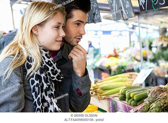 Young couple at greengrocer's shopping for fresh fruits and vegetables