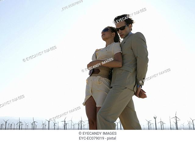Young stylish couple standing in front of wind farm