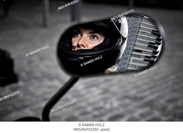 Young woman wearing motorcycle helmet reflected in wing mirror of a motorcycle