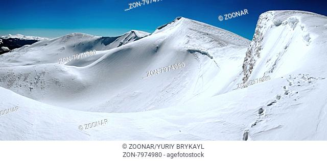 Winter mountains ridge with overhang snow caps on blue sky background (Ukraine, Carpathian , Svydovets Range, Blyznycja Mount)