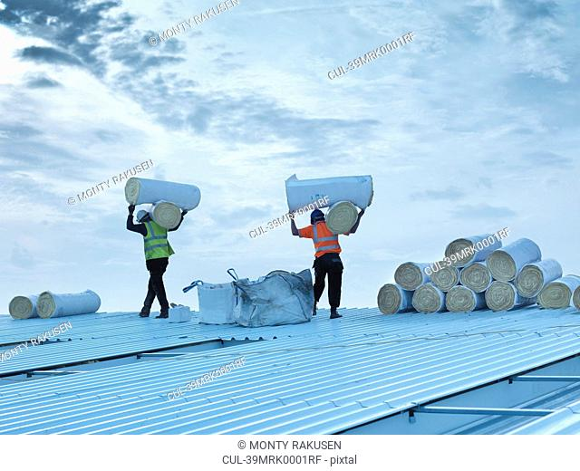 Workers carrying insulation on roof