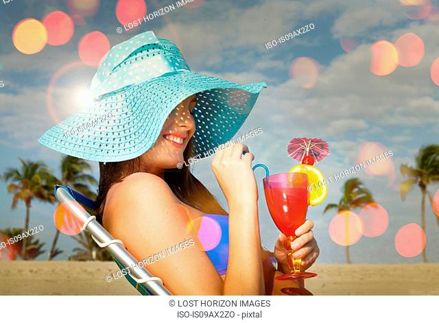 Young woman sitting on deckchair with cocktail at Miami beach, Florida, USA