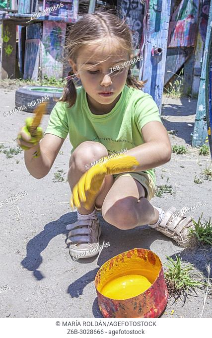 little girl playing with yellow paint