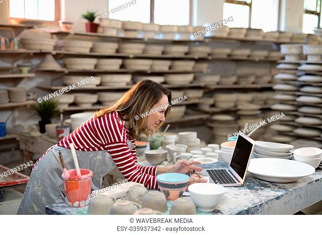 Female potter checking the orders from laptop