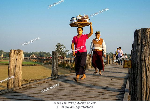 Woman with tanaka on her face carrying food on her head on a teak bridge, U Bein Bridge, over Thaungthaman Lake, Amarapura, Mandalay Division, Myanmar
