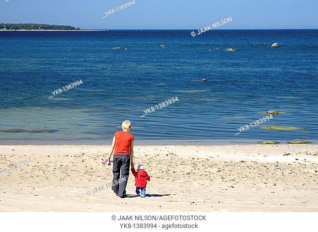 Mother and Daughter Walking Away Hand in Hand on Vääna-Jõesuu Beach by Baltic Sea, Estonia, Europe