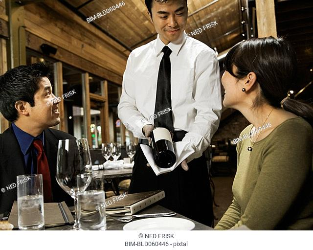 Asian waiter showing wine to couple