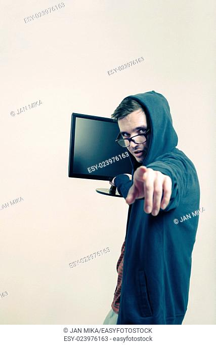 Man in hoodie holding monitor and pointing at you