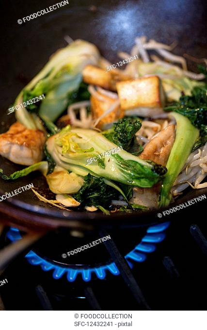 Bok choy with tofu and bean sprouts in a wok