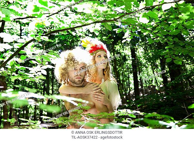 Young couple with blonde hair in woodland with sunlight