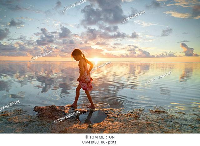 Girl wading in ocean surf on tranquil sunset beach