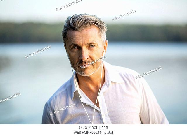 Portrait of man listening music with earphones at lake