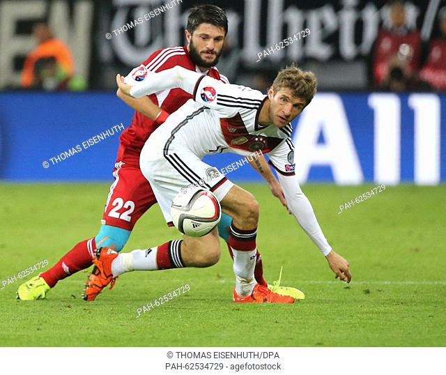 Germany's Thomas Mueller vies for the ball with Georgia's Giorgi Nawalowski during the European Championship qualification soccer match between Germany and...