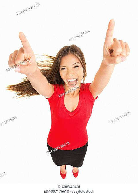 Successful woman cheering in jubilation laughing and pointing her hands to the sky, fun high angle full length studio portrait isolated on white background
