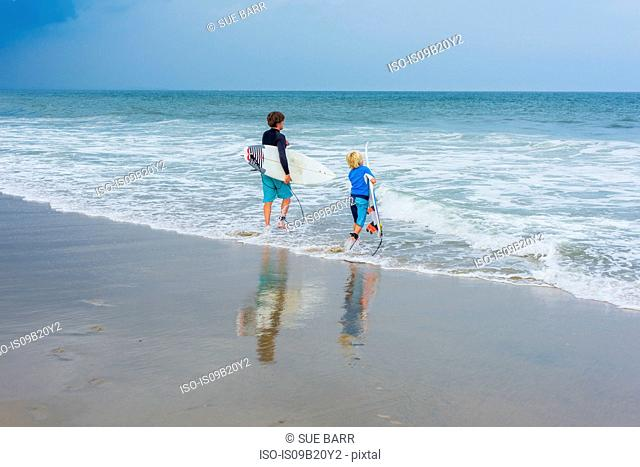 Father and son standing in sea, holding surfboards, rear view
