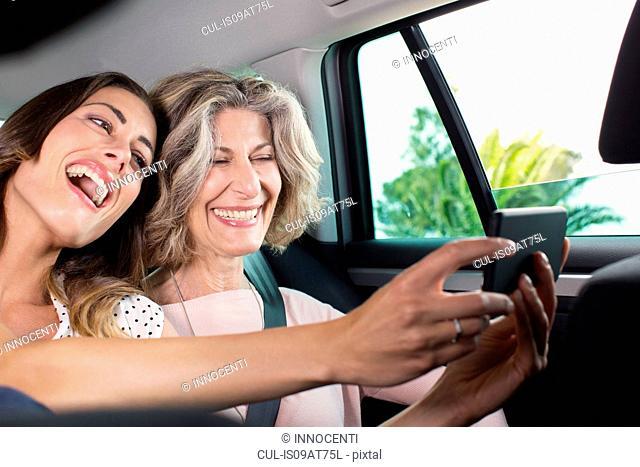 Senior woman and daughter taking smartphone selfie in car