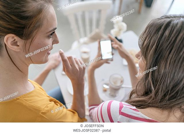 Two girlfriends meeting in a coffee shop, using smartphone