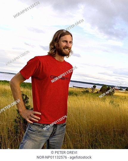 Young man smiling in the field with his hand on his hip, Gotland, Sweden