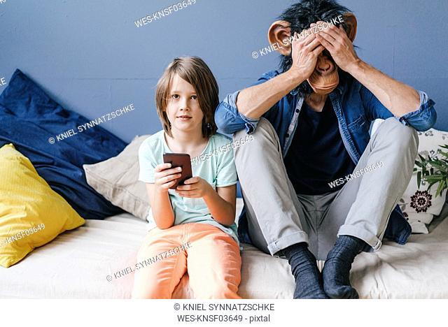 Father wearing monkey mask sitting next to son using smartphone at home