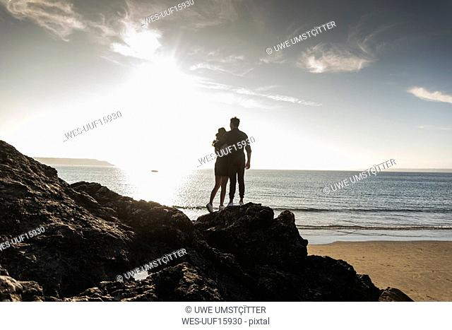 France, Brittany, rear view of young couple standing on rock at the beach at sunset