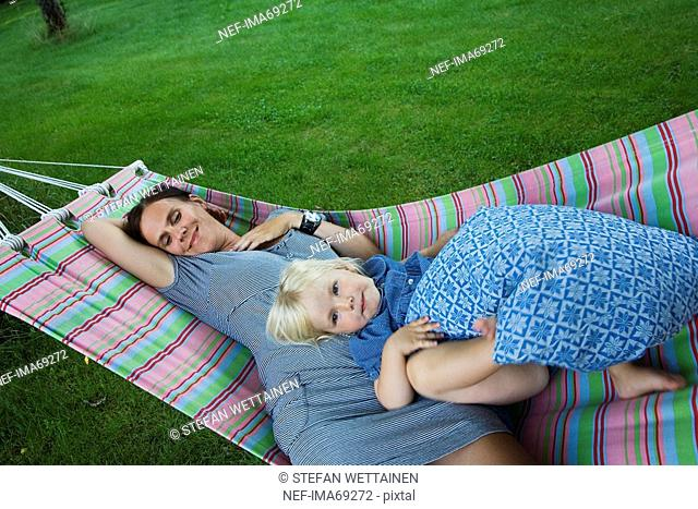 Mother and daughter resting in a hammock, Sweden