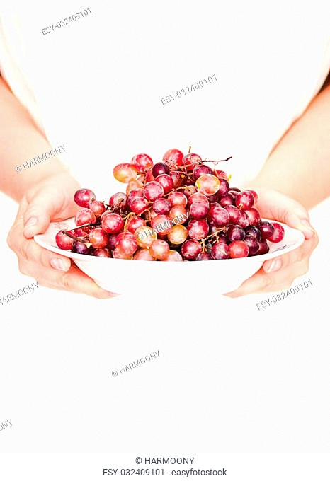 Hold in their hands a plate of fresh red grapes, whole plant foods,rustic
