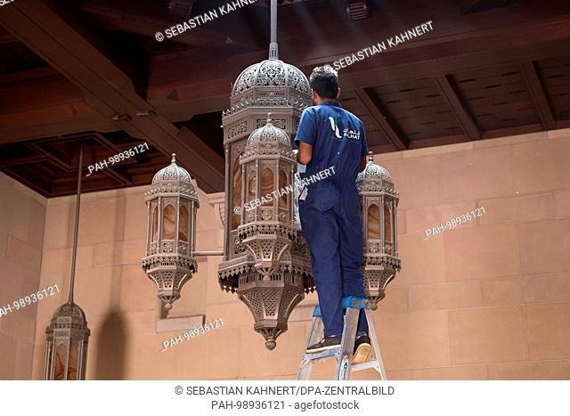 A caretaker cleaning a chandelier inside the Sultan Qaboos Grand Mosque in Muscat, Oman, on 01.10.2017. | usage worldwide. - Maskat/Maskat/Oman