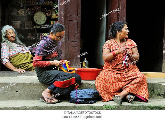 In the old town by the narrow street, so many women knitting by the road  Tow ladies working front of sweet shop