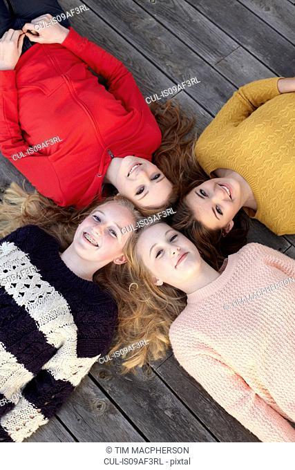 Portrait of four teenage girls head to head on patio