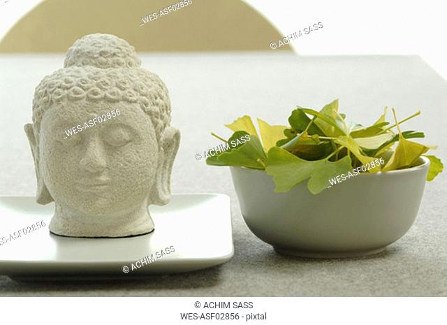 Buddha head by bowl with ginkgo leaves, close-up