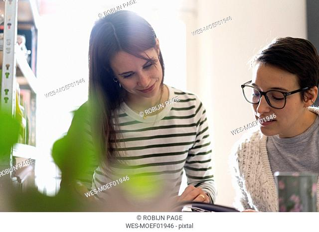 Two girlfriends at home reading magazine together