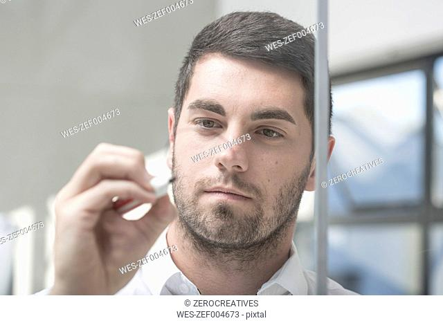 Businessman in office writing notes on glass