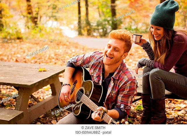 Young couple playing guitar on picnic bench in autumn forest