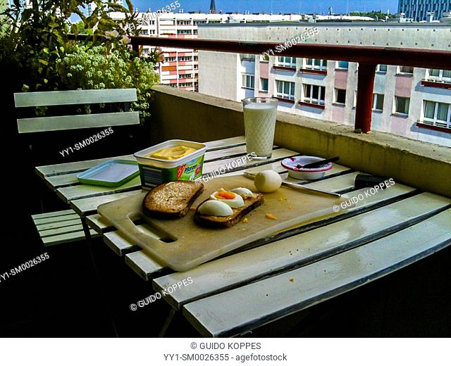 Berlin, Germany. Cozy breakfast at a plattenbau apartment's balcony during a sunny, summer morning